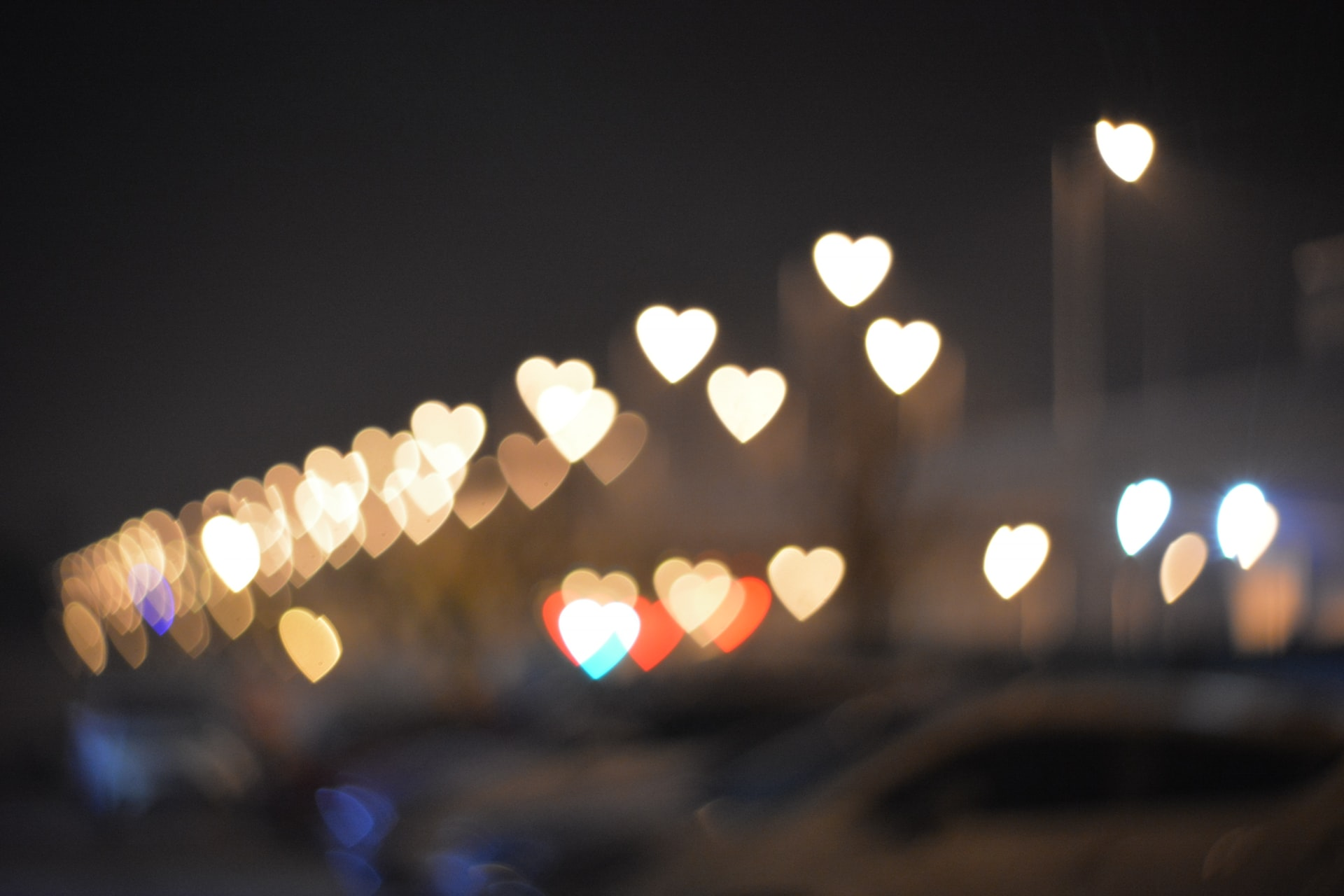 Heart-shaped lights in a variety of colors on a dark background