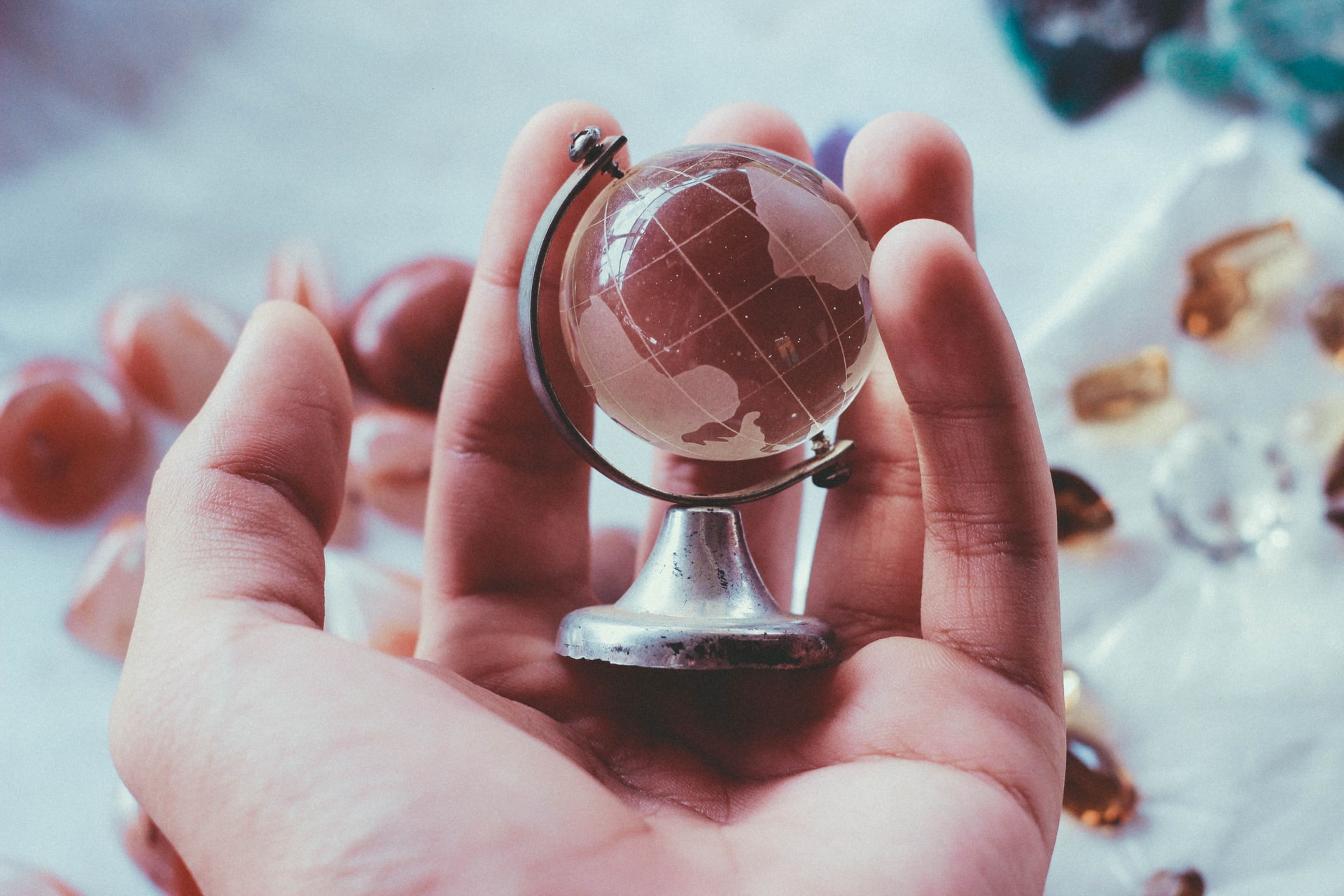 hand holding a small globe