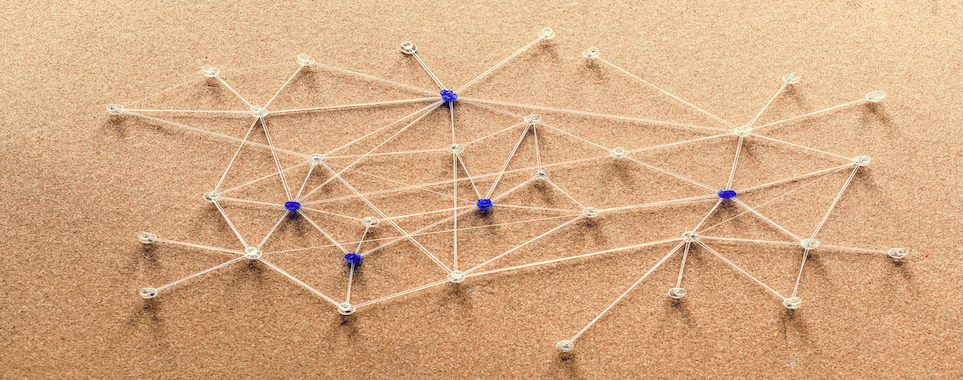 Blue and white pins connected by string on a cork board to illustrate a network