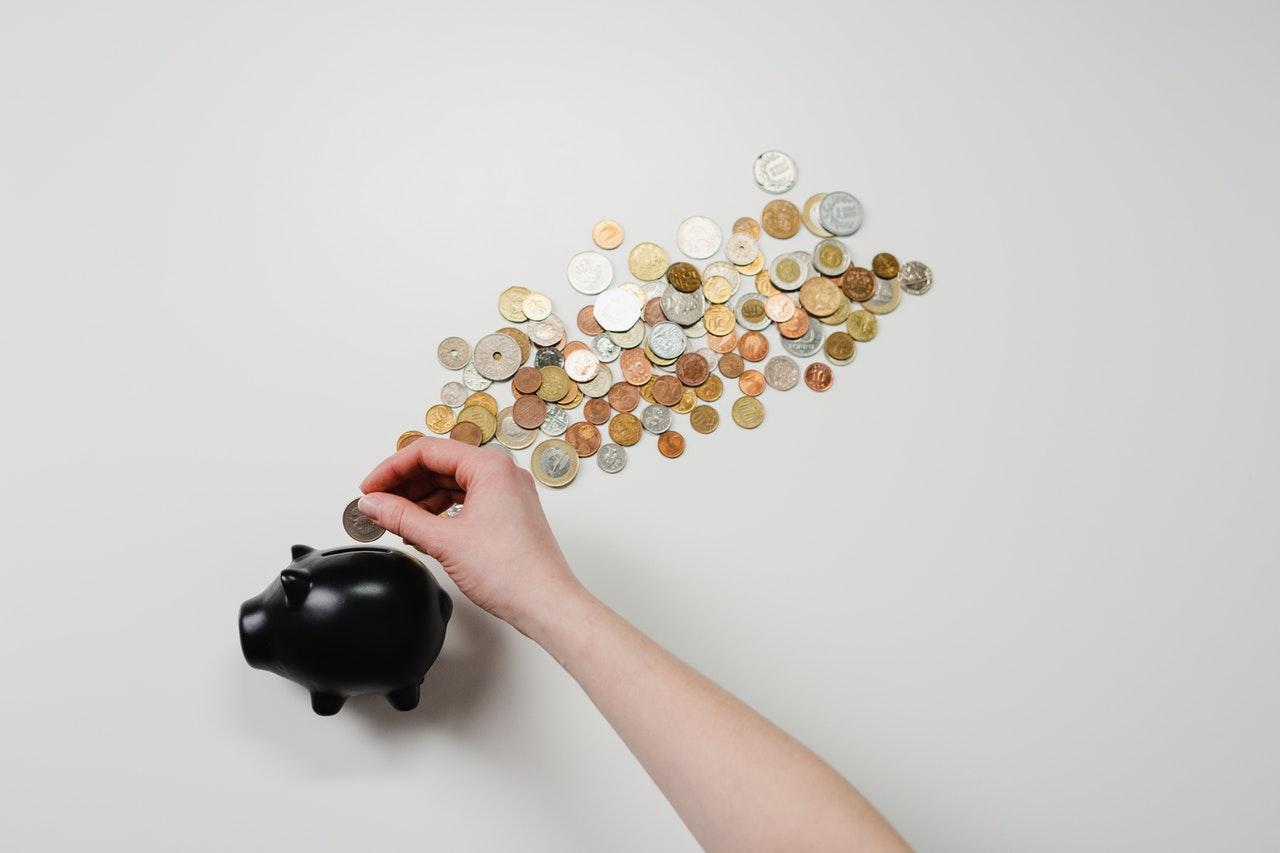 A person putting coins into a piggy bank