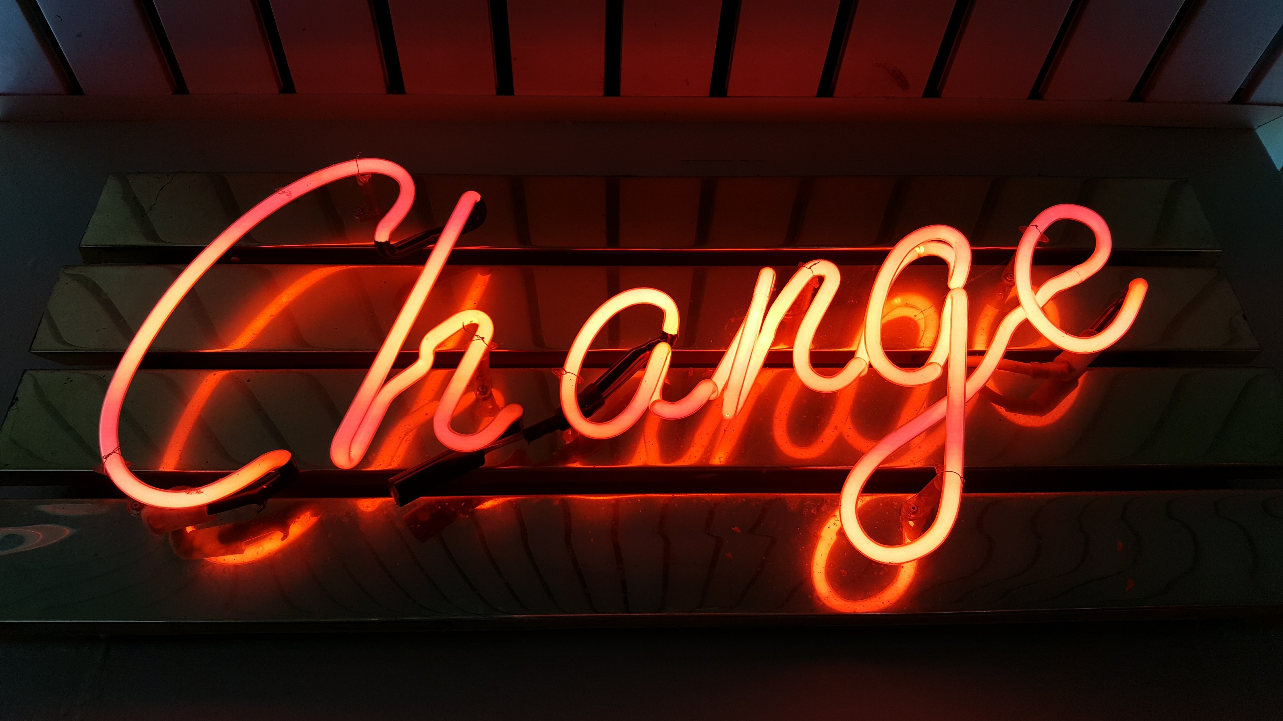 Orange neon letter sign that says Change