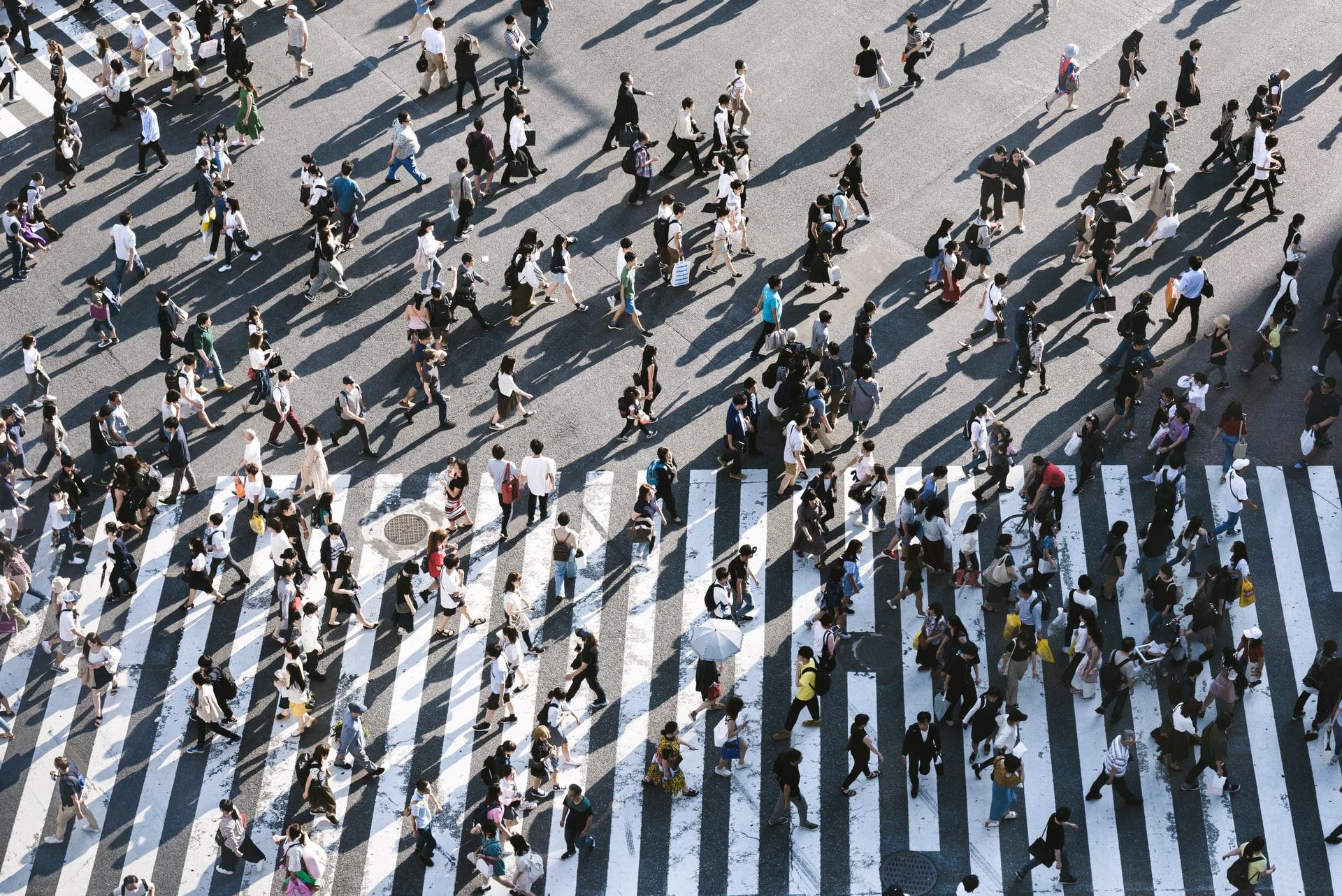 people walking through a crosswalk